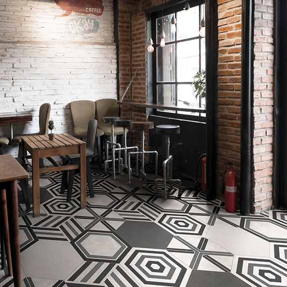 Rustic cafe with reclaimed brick walls and hexagon porcelain tile on the floor. Each hexagon tile has a different geometric pattern on it.