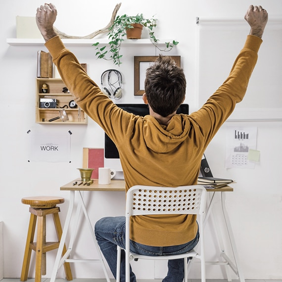 Back view of a teenaged male, sitting at a computer desk & chair, holding up his arms in celebration.