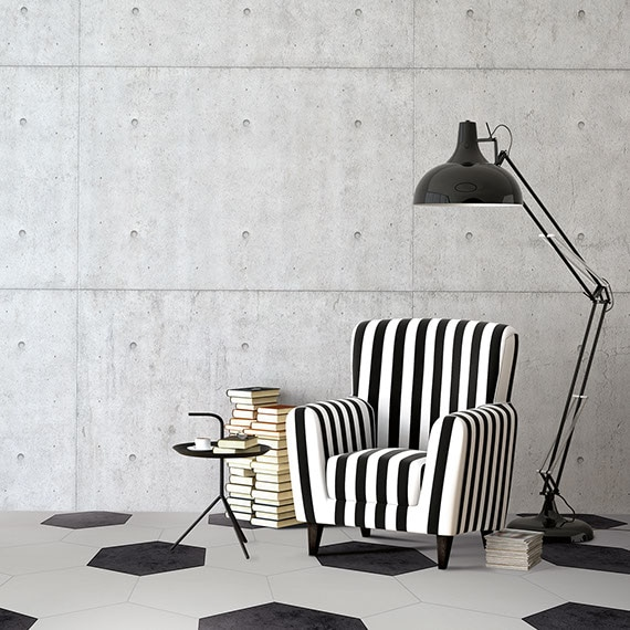 Sitting area with raw cement walls and black and white twenty-inch hexagon floors. Black and white striped armchair and black floor lamp in the background.
