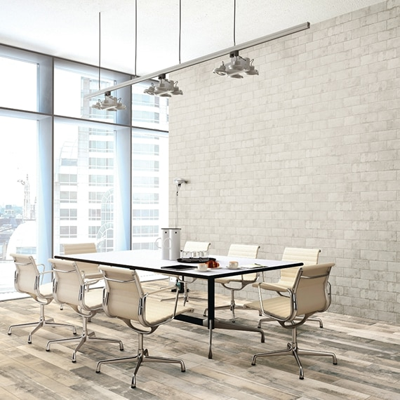Conference room with table, chairs, large windows, beige porcelain wall tiles that look like bricks and distressed wood floor tile.