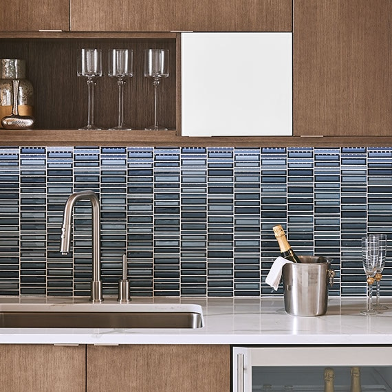 Kitchen with medium brown wood cabinets in a modern style with blue glass rectangular mosaic in a grid arrangement.