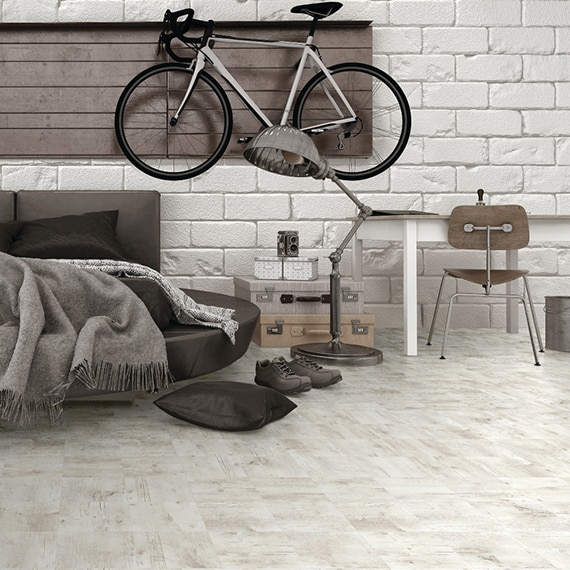 Scandinavian style apartment with light wood look tile floors, white brick wall with wood panel and bicycle hanging from it, gray couch, and desk & chair.