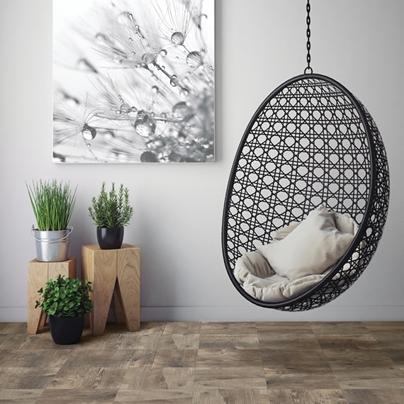 Hanging wicker chair, 10x10 wood look tile flooring with potted plants on wood pedestals and large black & white print on the wall.