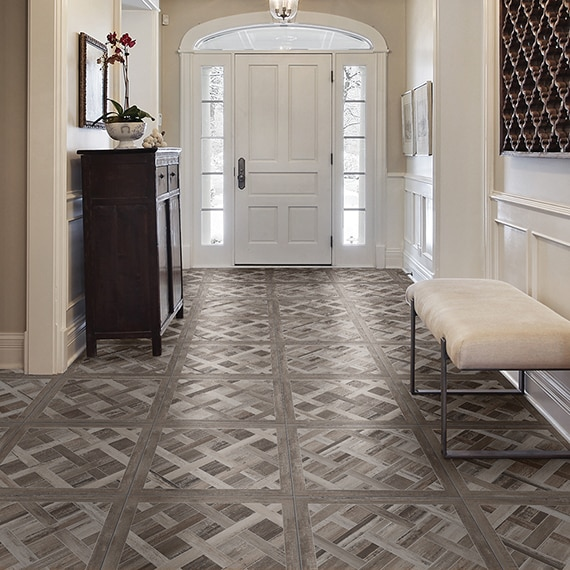 Residential foyer with floor tile that looks like wood in a cassettone pattern, white door with side windows, pendant lighting, and coffered ceiling.
