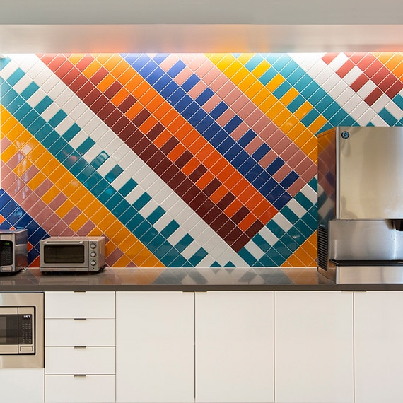 Breakroom with wall of bright blue, teal, red, orange, yellow, and white patterned tile, white lower cabinets, and stainless steel kitchen appliances.