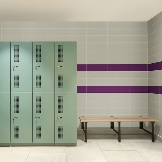 Locker room with 24x24 beige concrete look, beige wall tile with 2 purple horizontal stripes, mint green lockers and wood bench.