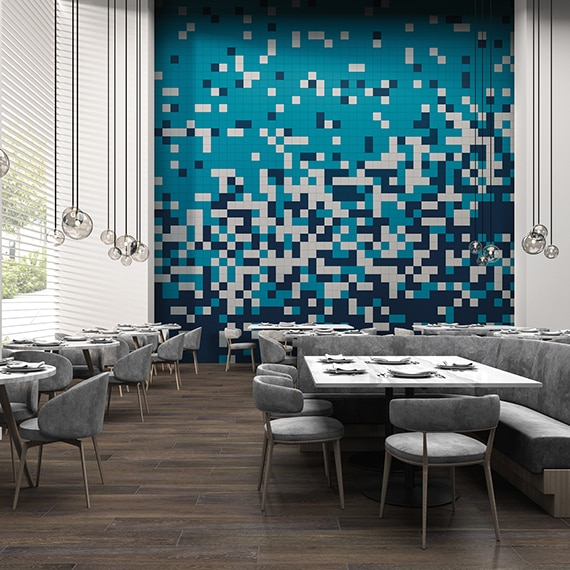 Restaurant dining room with 20-foot feature wall of navy, white, and teal tile in a random pattern, globe pendant lighting, wood look tile flooring, and tables with gray suede chairs & booths.