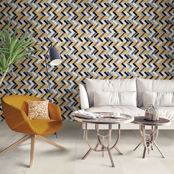 Sitting area with modern style furniture and a feature wall of gold, gray, and white mosiac rectangles in a herringbone pattern.
