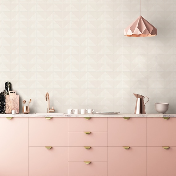 Breakroom counter with cream textured backsplash tile, marble countertop, peach pendant light & cabinets, copper faucet & carafe.