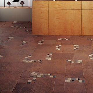 Boutiqe shop with chocolate brown slate-look tile on the floor with varied brown two inch mosaic as an accent. Shoe display in the background.