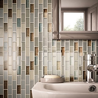 Small bathroom with feature wall behind the sink and mirror. One by two inch glass tiles in varying colors in gray, brown, and tan.