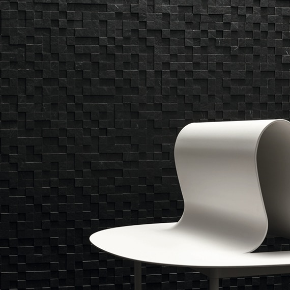 White abstract sculpture in front of black, 3D mosaic wall tile.