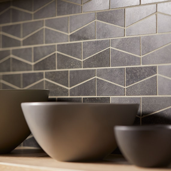 Kitchen backsplash with dark grey wedge-shaped mosaic tile. Three bowls on the countertop.