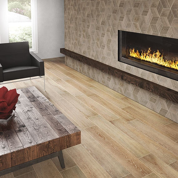 Living room with wood-look tiles for flooring, brown arm chair, and wall-mounted fireplace on wall with 3D-cube mosaic tile that looks like wood.