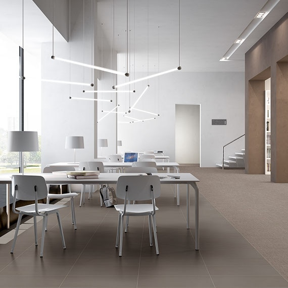 Library with large windows, study tables, and white bookshelves. Gray concrete-look porcelain tile floor.