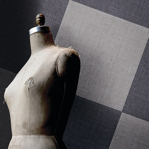 Navy and light gray fabric look tile in a checkered pattern on the wall behind well-worn sewing mannequin.