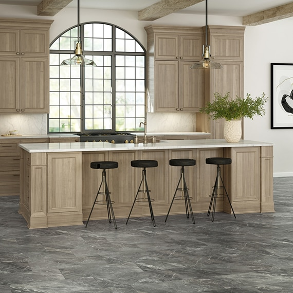 French country kitchen with gray stone look tile floor, wood cabinets, ivory/beige marble island countertop & backsplash, arched picture window.