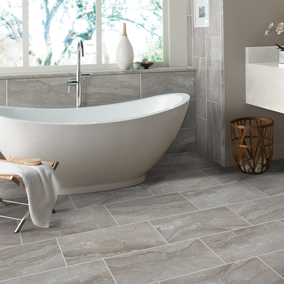 Bathroom with freestanding bathtub, antimicrobial treatment on gray marble look tile on the floor and backsplash, in front of picture window.