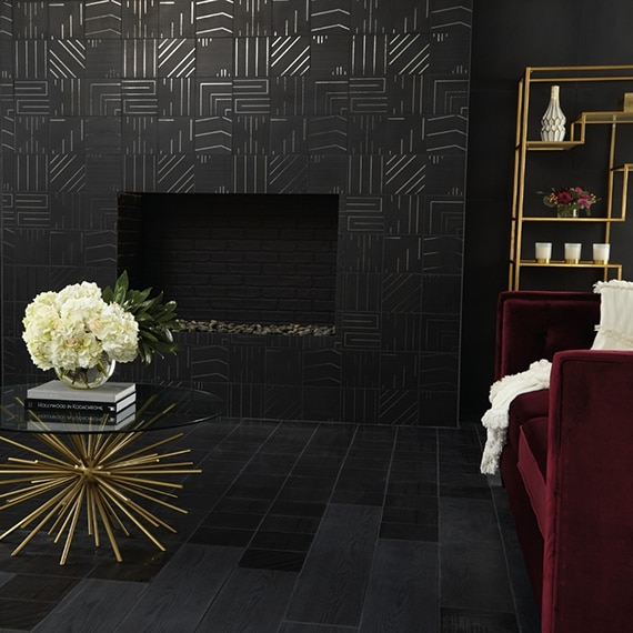 Living room fireplace with black geometric tile, crimson velvet chairs, coffee table with bouquet of white hydrangeas, and black wood look tile.