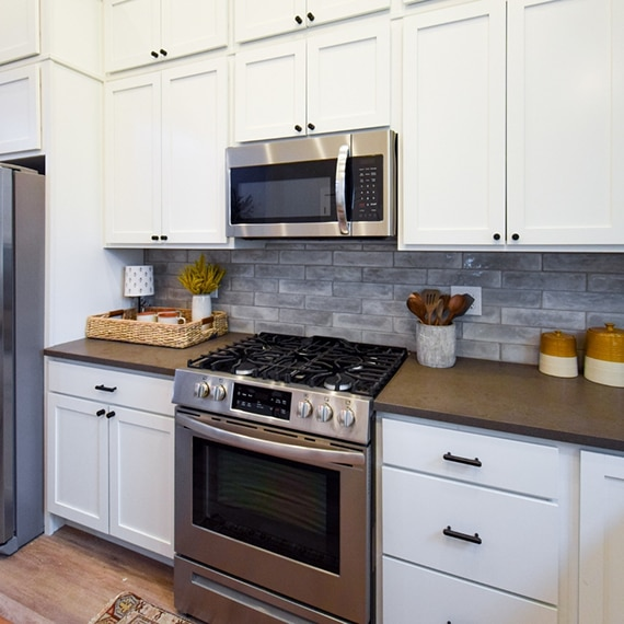 Kitchen with brown quartz countertops, cream cabinets, gray subway tile backsplash, and stainless steel stove/oven.