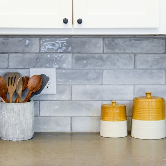 Closeup of high gloss gray subway tile kitchen backsplash, brown quartz countertop, stone vase holding wooden spoons, and white & yellow ceramic containers.