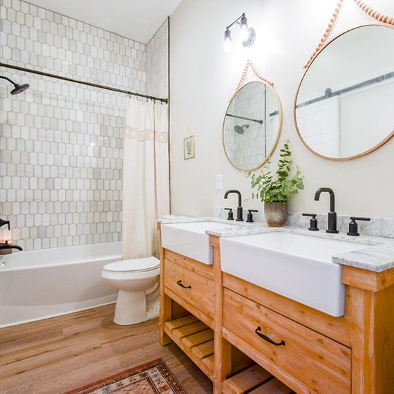 Bathroom with shower/tub with cream & gray ingot marble mosaic tile walls, white & gray marble vanity counter with natural wood cabinet.