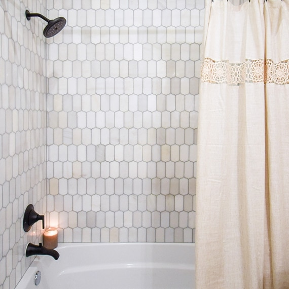 Shower/tub with cream & gray ingot marble mosaic tile walls, black showerhead and faucet, candle, and off-white shower curtain.
