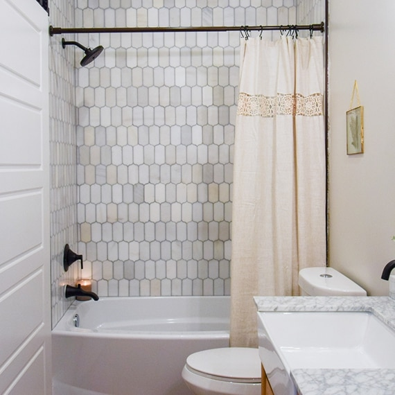 Bathroom with shower/tub with cream & gray ingot marble mosaic tile walls, white & gray marble vanity counter, and off-white shower curtain.