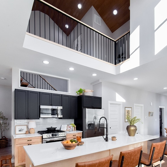 Kitchen open to second floor with white quartz countertops & island, white mosaic backsplash, black upper cabinets, and natural wood lower cabinets.