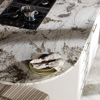 Rounded edge kitchen peninsula with cooktop and dramtic dark gray and white natural stone countertop.