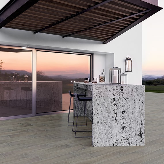 Backyard coverd patio with tiled floor and natural stone black and white waterfall bar.