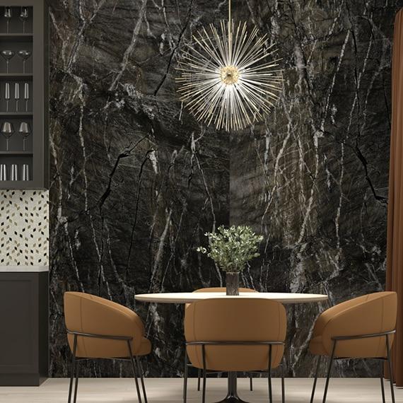 Dining room with stunning walls of black granite slab with white veining, and starburst lighting over table with four tan leather chairs.