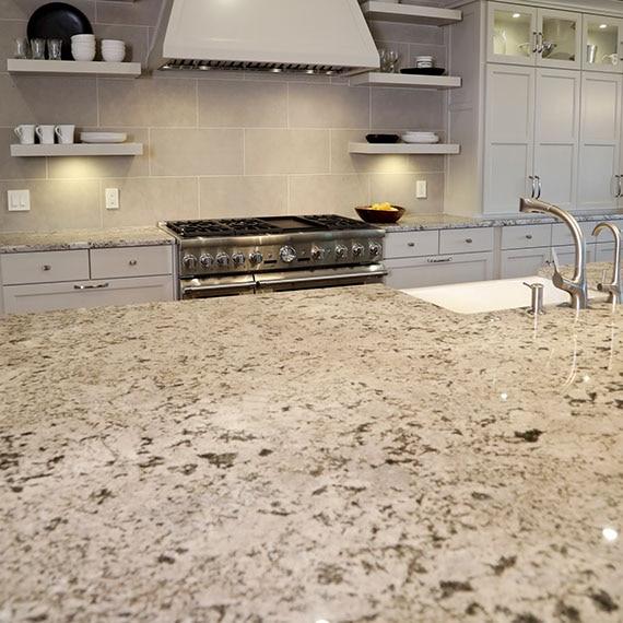 Kitchen with beige & brown granite island with built-in sink, beige limestone backsplash, beige cabinets, hood vent, and floating shelves.