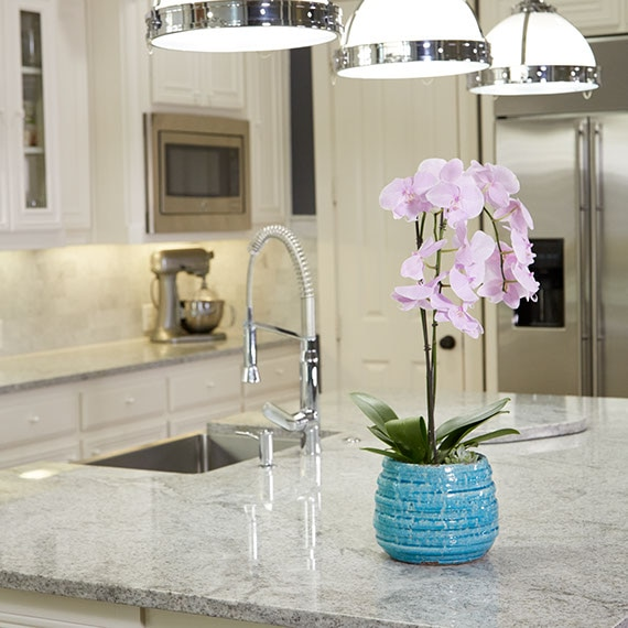 Large kitchen island with white and grey granite. Orchid in blue pot on the counter next to the sink.