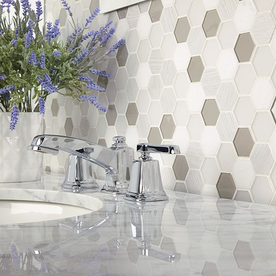Closeup of bathroom backsplash of white, off-white, and gray stone and glass mosaic tile, marble countertop, polished silver faucet, and bouquet of lavender.