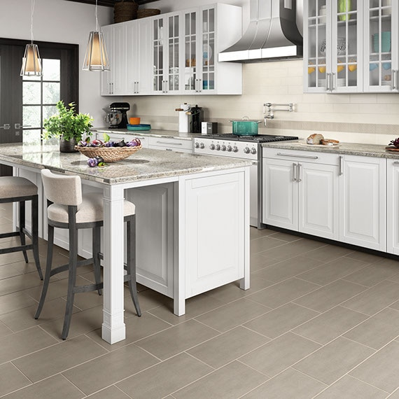 Kitchen with white cabinets and island. Lathe-turned corner post supporting island countertops. Concrete-look twelve by twenty-four inch porcelain tile floor in a light grey.