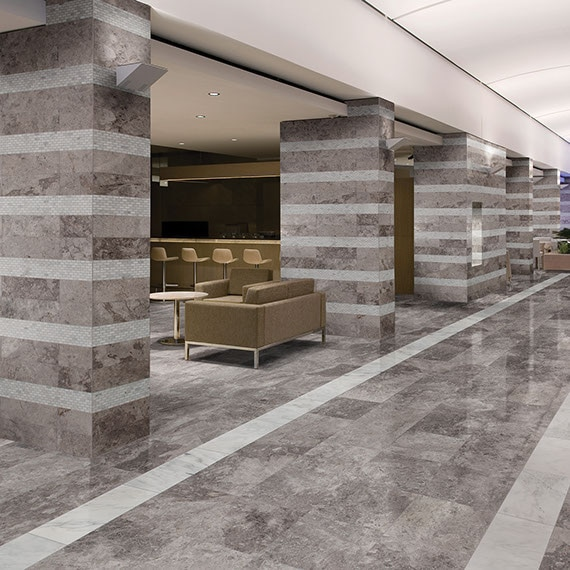 Lobby with desk and seating in the background and columns in the foreground. Silver gray limestone on the floors and columns with white limestone stripes on the columns.