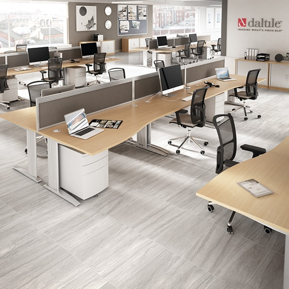 Open concept office with gray stone look floor tile, black rolling chairs, wood top desks holding laptops and monitors with keyboards.