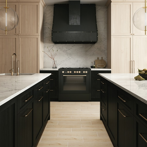 Modern kitchen with two islands, white marble with gray & beige veining countertops & backsplash, black lower cabinets, and natural wood upper cabinets.