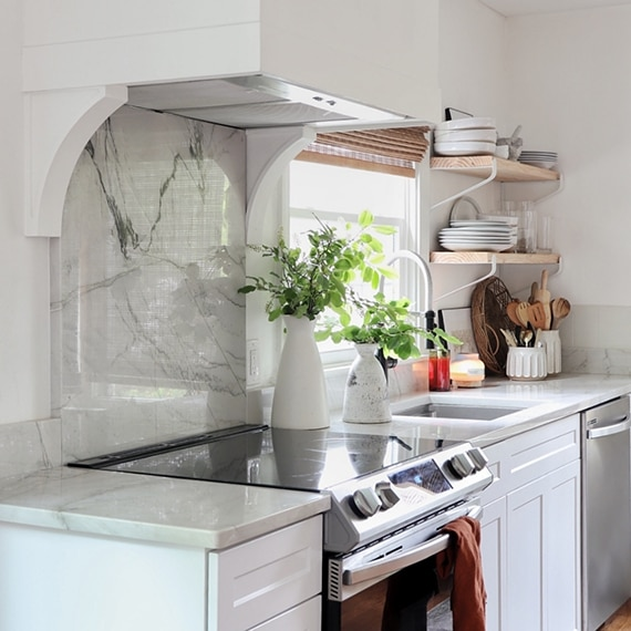 Kitchen with natural quartzite countertops & backsplash, white hood vent, wood floating shelves, and vases with greenery.