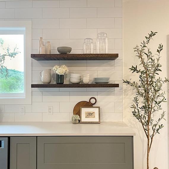 Kitchen backsplash of white subway tile, natural wood floating shelves, white quartz countertops, and gray lower cabinets.