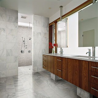 Modern style bathroom with dark wood cabinets and white marble covering the floor and walls. Large walk-in shower in the background.