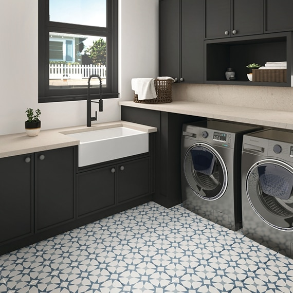Laundry room with blue & white encaustic floor tile in herringbone pattern, front-loading washer and dryer, brown cabinets, off-white quartz counters, and white subway wall tile.