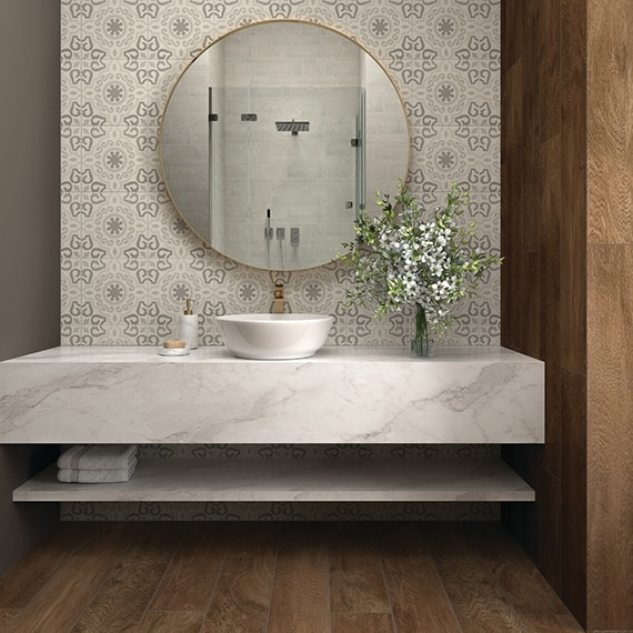 Bathroom vanity with round mirror on a white & gray encaustic tile backsplash, and vessel sink on white quartzite countertop with gray veins.