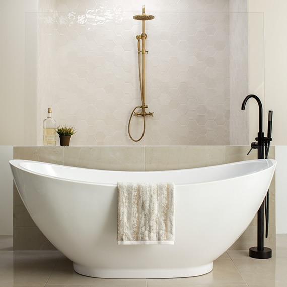 White free-standing soaker bathtub with black faucet in front of open shower, beige floor tile and beige hexagon shower wall tile that looks like stone.