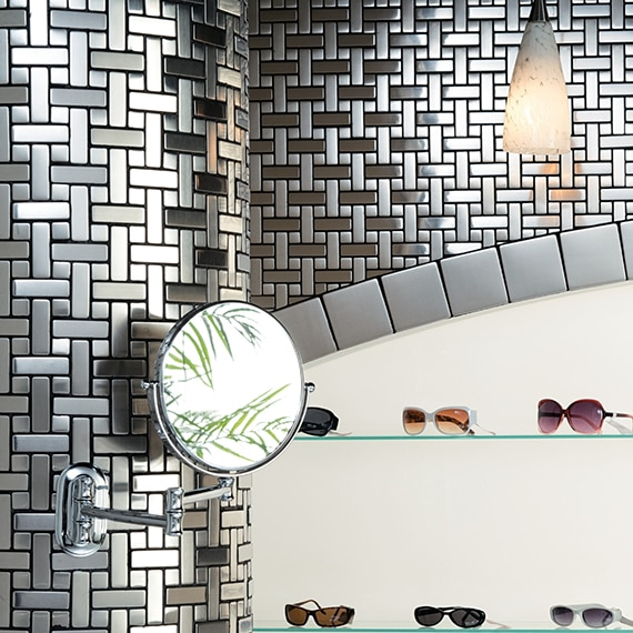 Sunglass store with brushed steel mosaic wall tile with inset glass shelves trimmed with 4x4 metal tile, holding sunglasses.
