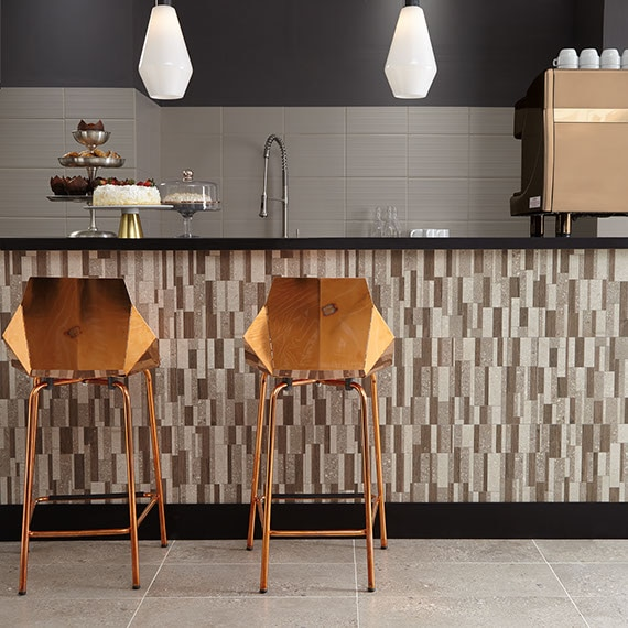 Kitchen island bar with cakes on stands on the countertop. Modern style bar stools with backs. Island front tiled with random block mosaic in varigated colors from grey to taupe.