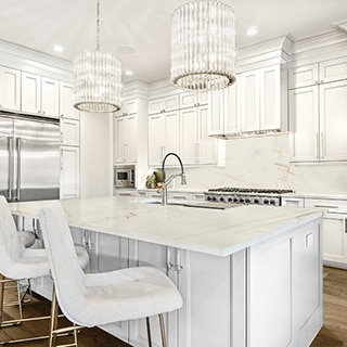 Eat-in kitchen with pendant lighting, white & tan quartzite counters, island with built in sink, white cabinets, stainless steel gas stove and refrigerator.