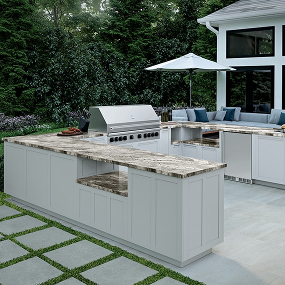 Outdoor kitchen with tan heavily veined quartzite countertops on white cabinets, stainless steel grill, gray stone-look tile flooring, and gray stone-look pavers set in grass.