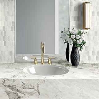 Bathroom with white marble vanity and white marble ingot mosaic backsplash.